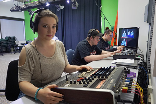 female student working at soundboard in video studio